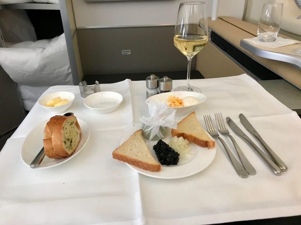 Kaviar med traditionella tillbehör, vitlöksbröd på sidan och den goda Rieslingen